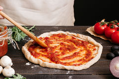 Cooking pizza. Hands adding fresh tomato sauce to pizza dough. Pizza ingredients on the wooden table Royalty Free Stock Images