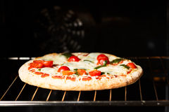 Cooking pizza in oven Royalty Free Stock Images