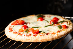 Cooking pizza in oven shallow DOF Royalty Free Stock Photo