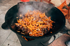 Cooking plov in the cauldron. Only meat, onions and carrots in t Royalty Free Stock Image
