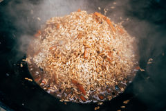 Cooking plov in the cauldron. Rice, meat, onions and carrots in Royalty Free Stock Photography