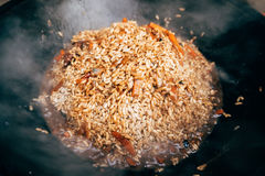 Cooking plov in the cauldron. Rice, meat, onions and carrots in Royalty Free Stock Image