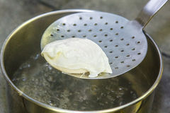 Cooking poached eggs. The egg is pulled out of the water with a slotted spoon Royalty Free Stock Image