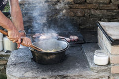 Cooking polenta on wood stove Royalty Free Stock Photo