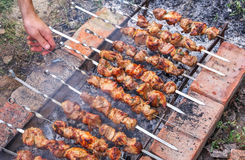 Cooking pork kebabs on the grill. Man's hand turn over kebabs on. A grill for better quality of preparation Royalty Free Stock Photo