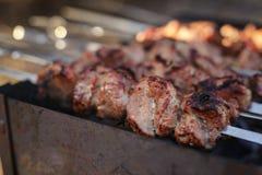 Cooking pork shashlik on skewer in mangal outdoor Royalty Free Stock Photography