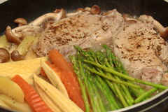 Cooking pork steak with mixed vegetables for served. Stock Photo