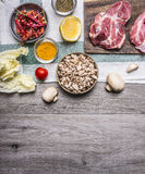 Cooking pork steaks on the cutting board, on a napkin, mushrooms, spices, tomato border, place for text  on wooden rustic backgrou. Cooking pork steaks the Stock Images