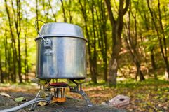 Cooking on a portable gas burner in outdoor conditions hikes.  Royalty Free Stock Image