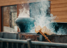 Cooking in pot. Cook in a cast iron pot on the fire Stock Photos
