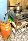 Cooking pot on gas stove. Cooking food in a pot on a gas stove, which is attached to a gas tank via a flexible pipe, in a kitchen of a typical HDB flat in royalty free stock images