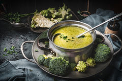 Cooking pot with green romanesco and broccoli soup and ladle on dark rustic kitchen table . Healthy food and diet nutrition. Concept Stock Photography