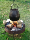 Cooking pot over fire. Cauldron hanging over fire at campsite stock photography
