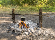 Cooking in a pot over the fire. Cooking in a pot over the campfire in wild camping stock images