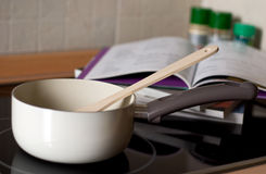 Cooking pot on a stove. With recipe book in distance Stock Photo