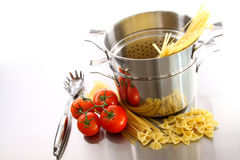 Cooking pot with uncooked pasta and tomatoes Stock Images