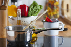 Cooking Pot with Wooden Spoon on Ceramic Hob Royalty Free Stock Photos