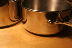 Cooking Pots. Metallic pots sitting on a wooden table Royalty Free Stock Images