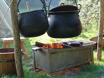 Cooking pots over fire. Cauldrons hanging over fire at medieval campsite stock image