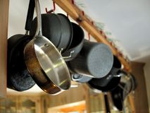 Cooking pots and pans hanging in kitchen. Cooking pots and pans hanging in kitchen from ceiling Stock Photo