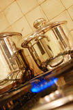 Cooking pots on stove. Metal cooking pots on a stove with gas flame underneath Stock Image