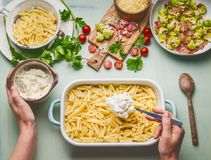 Cooking preparation of American style hearty macaroni pasta in cheesy sauce. Female hand making pasta casserole. With tomato, bacon and cheese, top view Stock Photography