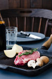 Cooking preparation in the kitchen with raw beef steak. Dining table with raw beef steak in a cast iron pan with potatoes and mushrooms, dinner preparation ready Royalty Free Stock Images