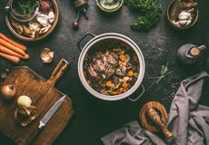 Free Cooking Preparation Of Stewed Meat. Roasted Beef Meat In Cast Iron Cooking Pot With Vegetables On Dark Rustic Background With Stock Photography - 137304272