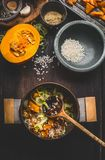Cooking preparation with  pot of vegetarian pumpkin risotto and spoon on dark rustic kitchen table background with cooking ingredi. Cooking preparation with pot Royalty Free Stock Photo