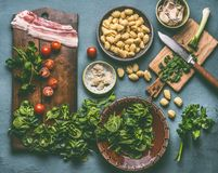 Cooking preparation of Potato gnocchi meal with spinach,tomatoes and bacon on rustic table. Background , top view royalty free stock image