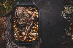 Cooking preparation of venison roast. Leg of deer with bone in cast iron pan with gut vegetables on dark kitchen table background. With herbs and spices. Copy royalty free stock photo