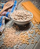 The cooking process. A bowl of raw oatmeal, cereals, pasta, wooden spoon and a towel on a wooden table. Preparation of morning breakfast Royalty Free Stock Photo