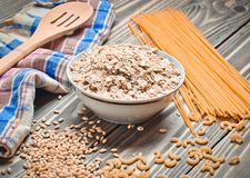 The cooking process. A bowl of raw oatmeal, cereals, pasta, wooden spoon and  towel on a wooden table. Preparation of morning bre. The cooking process. A bowl of Stock Photo