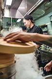 Cooking process. Close up of chef`s hand holding wooden lid while preparing food with his two assistants in a restaurant. Kitchen. Vertical photo. Culinary stock photography