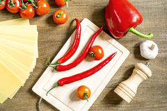 Cooking process in the kitchen. Vegetables spaghetti kitchen utensils laid out on the rough wooden table top view Stock Photography