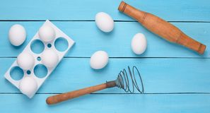 The cooking process. Plastic tray with white eggs, rolling pin, royalty free stock photos