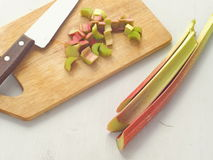 Cooking process. Preparing rhubarb cake. Rhubarb stems arranged on old wooden background, whole and cut on pieces. Stock Photos
