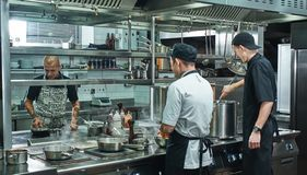 Cooking process. Professional team of chef and two young assistant preparing food in a restaurant kitchen. Teamwork royalty free stock photography