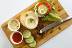 Cooking process of a sandwich burger, ingredients on wooden cutting board on wooden table against white background, fresh vegetabl Stock Photo