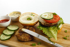 Cooking process of a sandwich burger, ingredients on wooden cutting board on wooden table against white background, fresh vegetabl. Es, herbs, fried meat, buns Royalty Free Stock Image