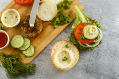 Cooking process of a sandwich burger, ingredients on wooden cutting board on wooden table against white background, fresh vegetabl Stock Photos