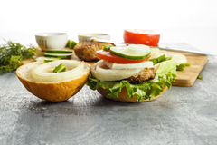Cooking process of a sandwich burger, inredients on wooden cutting board on wooden table against white background, fresh vegetable Stock Photo