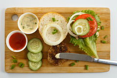 Cooking process of a sandwich burger, inredients on wooden cutting board on wooden table against white background, fresh vegetable Stock Images