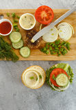 Cooking process of a sandwich burger, inredients on wooden cutting board on wooden table against white background, fresh vegetable Royalty Free Stock Photo