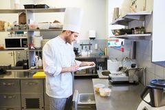 Chef with clipboard doing inventory at kitchen Royalty Free Stock Images
