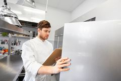 Chef with clipboard doing inventory at kitchen. Cooking, profession and people concept - male chef cook with clipboard doing inventory and looking to fridge at Stock Images