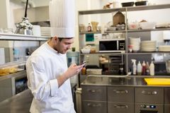 Chef cook with smartphone at restaurant kitchen Royalty Free Stock Image