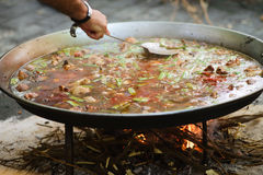 Cooking of a raditional spanish dish paella. Prosess of cooking traditional spanish dish paella on fire Stock Photos