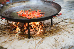 Cooking of a raditional spanish dish paella. Prosess of cooking traditional spanish dish paella on fire. Red peper Stock Images