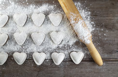 Cooking ravioli. Cooking dumplings. Raw heart shaped dumplings, flour and rolling pin on wooden background. Top view Stock Image